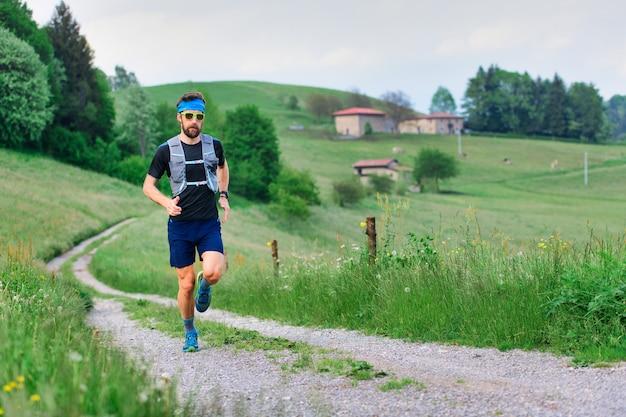 Młody sportowiec z brodą działa w wiejski krajobraz wzgórza