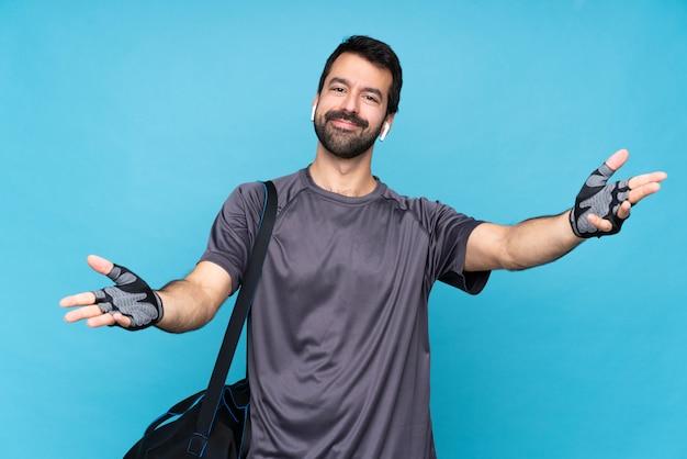Młody sportowiec z brodą na pojedyncze niebieskie ściany, prezentując i zapraszając do strony