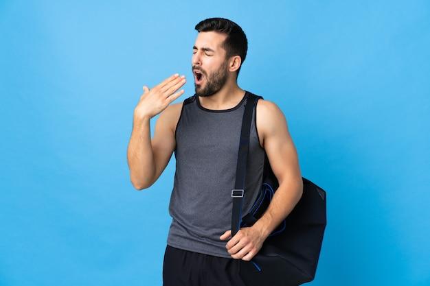Młody sportowiec z torbą sportową na białym tle na niebieskim tle ziewanie i obejmowanie ręką szeroko otwarte usta