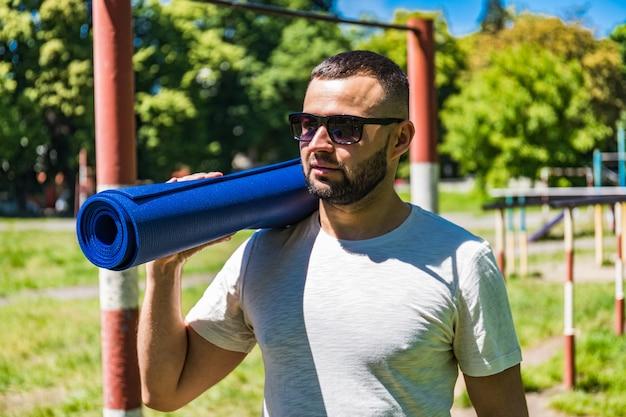 Młody sportowiec zakończył swoją pracę. sportowiec w parku. mężczyzna z niebieską matą do jogi. medytacja i relaksacja.