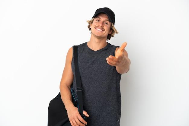 Młody sportowiec ze sportową torbą na białym tle drżenie rąk za zamknięcie dobrej oferty good
