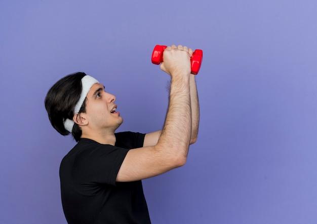 Młody sportowy człowiek ubrany w odzież sportową i opaskę, ćwicząc z hantlami, wyglądający na zmęczonego i zdezorientowanego