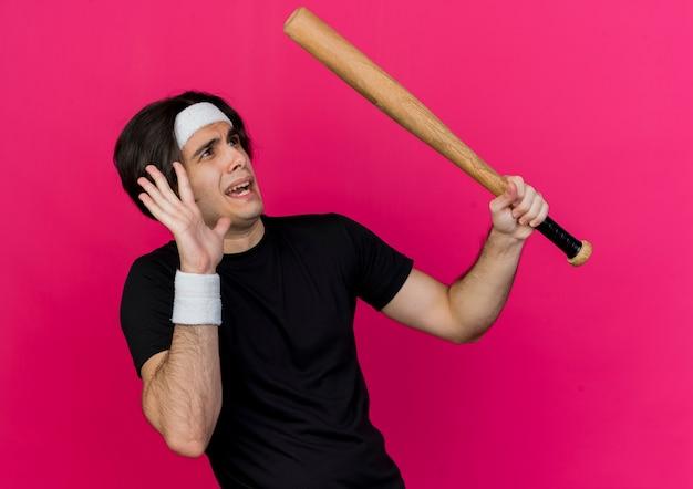 Młody sportowy człowiek ubrany w odzież sportową i pałąk trzymając kij baseballowy, patrząc na coś przestraszonego, robiąc gest obrony ręką