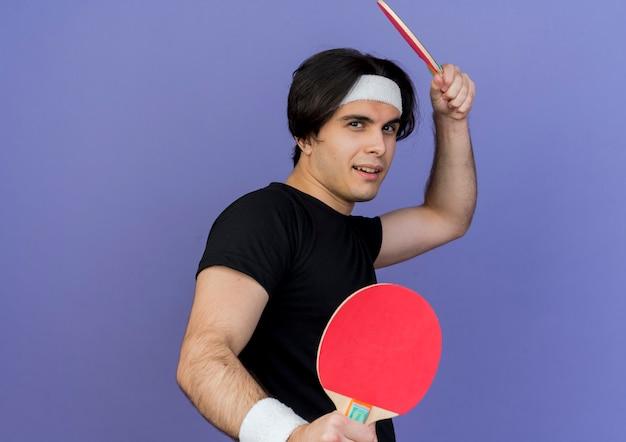 Młody sportowy człowiek ubrany w odzież sportową i pałąk trzymając rakiety do tenisa stołowego z poważną miną