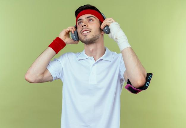 Młody sportowy człowiek w opasce ze słuchawkami i opaską na ramię smartfona szczęśliwy i pozytywny, ciesząc się jego muzyką stojąc na zielonym tle