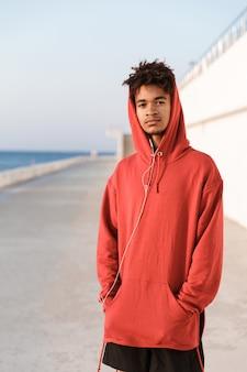 Młody sportowy facet na zewnątrz na plaży patrząc kamery