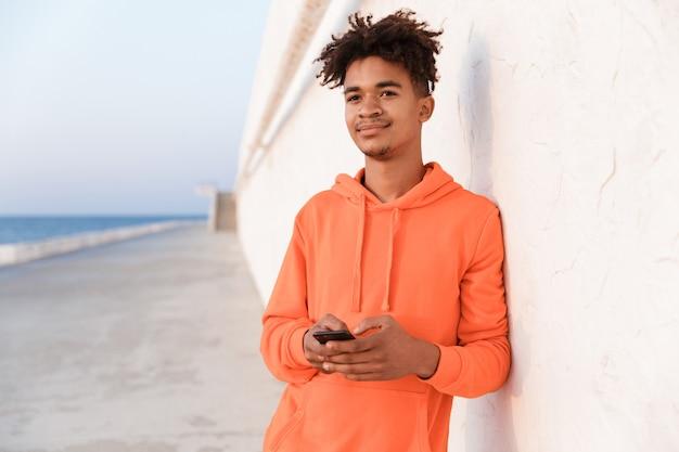 Młody sportowy facet na zewnątrz na plaży przy użyciu telefonu komórkowego