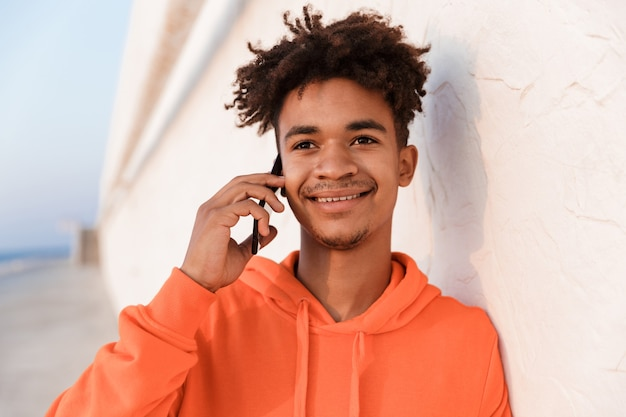 Młody sportowy facet na zewnątrz na plaży rozmawia przez telefon komórkowy