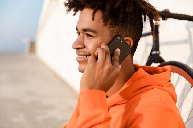 Młody sportowy facet na zewnątrz na plaży z rowerem rozmawia przez telefon komórkowy