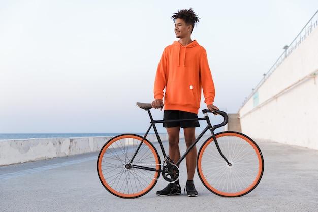 Młody sportowy facet na zewnątrz na plaży z rowerem
