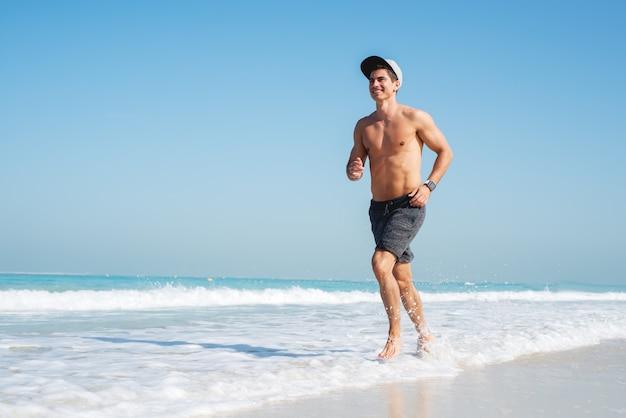 Młody sportowy mężczyzna biegnie wzdłuż pięknej plaży, patrząc szczęśliwy.