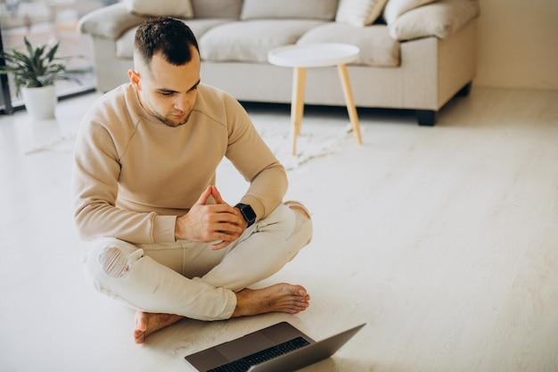 Młody sportowy mężczyzna ćwiczący jogę w domu