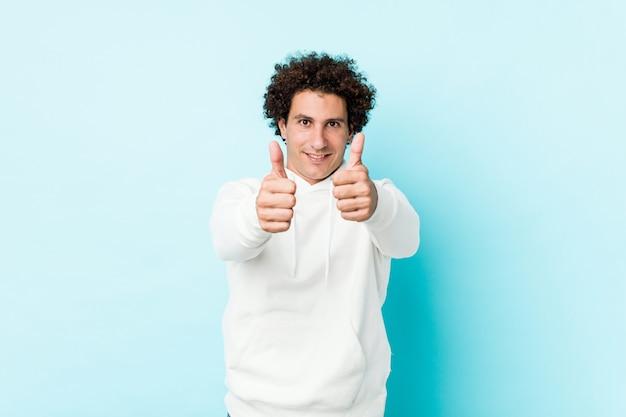 Młody sportowy mężczyzna na niebieskim tle z kciukami do góry, na zdrowie o coś