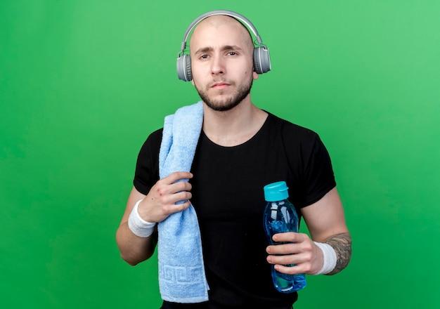Młody sportowy mężczyzna na sobie opaskę i słuchawki, trzymając butelkę wody z ręcznikiem na ramieniu