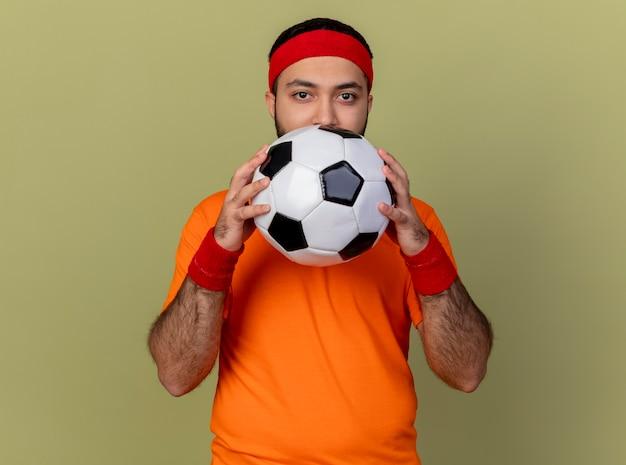 Młody sportowy mężczyzna patrząc na kamery noszenie opaski i nadgarstka trzymając piłkę na białym tle na oliwkową zieleń