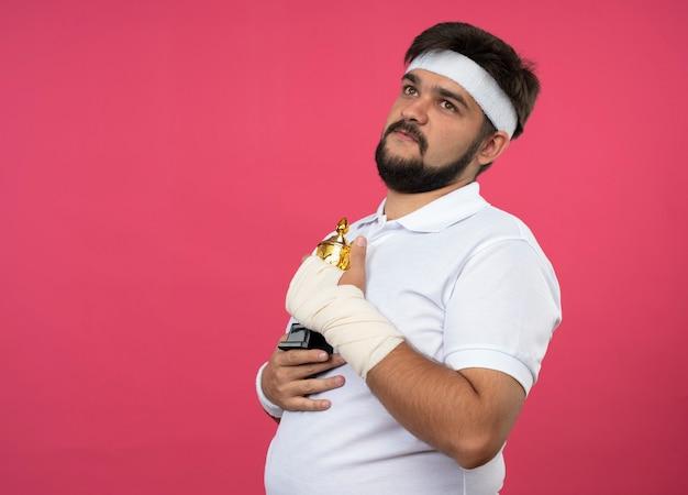 Młody sportowy mężczyzna patrząc z boku z opaską na głowę i opaską z nadgarstkiem owiniętym bandażem trzymającym kubek zwycięzcy odizolowany na różowej ścianie z miejscem na kopię