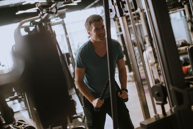 Młody sportowy mężczyzna pracujący na rozwijanej maszyny w siłowni