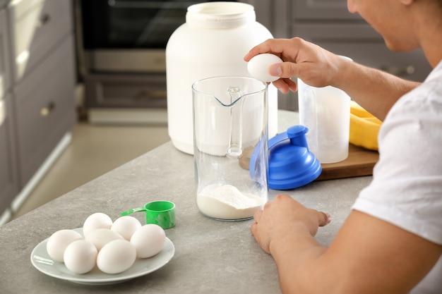 Młody sportowy mężczyzna przygotowuje shake proteinowy przy stole