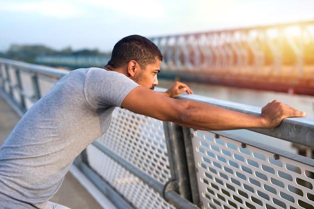 Młody sportowy mężczyzna skoncentrowany na treningu skupiony sportowiec patrząc na rzekę o zachodzie słońca. sportowiec przygotowuje się do biegania. fitness i zdrowy tryb życia.