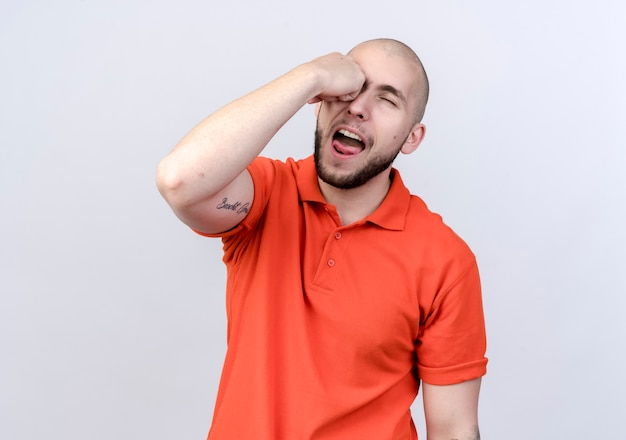 Młody sportowy mężczyzna trzyma pięść na oku na białym tle na białej ścianie