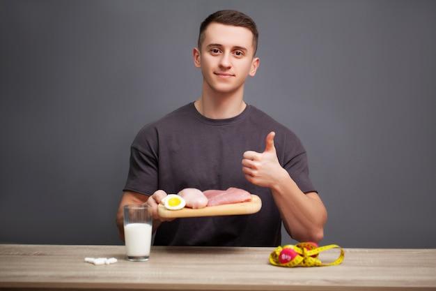 Młody sportowy mężczyzna trzyma posiłek wysokobiałkowy dla dobrego odżywiania