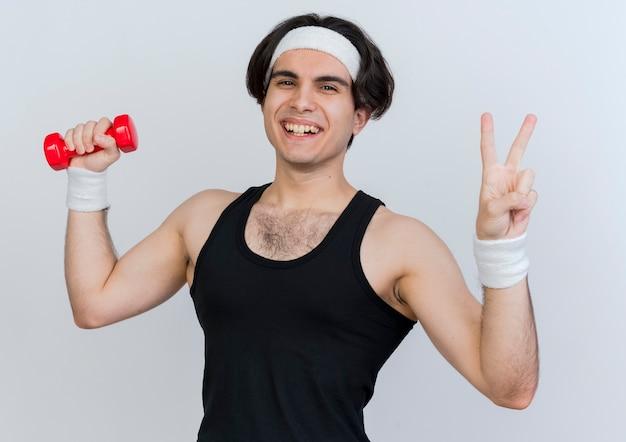 Młody sportowy mężczyzna ubrany w odzież sportową i opaskę, ćwicząc z hantlami, uśmiechając się z radosną buzią pokazując znak v stojący nad białą ścianą