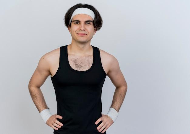 Młody sportowy mężczyzna ubrany w odzież sportową i opaskę, patrząc na przód, uśmiechnięty pewnie z rękami na biodrze, stojąc na białej ścianie