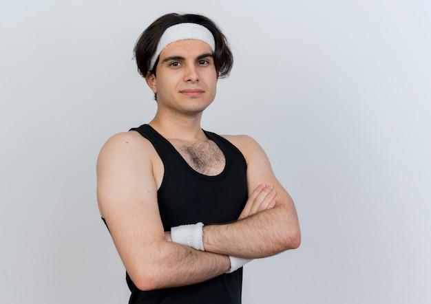 Młody sportowy mężczyzna ubrany w odzież sportową i opaskę, patrząc z przodu z pewnym uśmiechem ze skrzyżowanymi rękami na klatce piersiowej stojącej nad białą ścianą