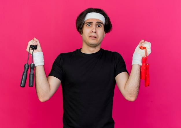 Młody sportowy mężczyzna ubrany w odzież sportową i opaskę trzymającą dwie skakanki wyglądający na zdezorientowanego i niepewnego, próbującego dokonać wyboru