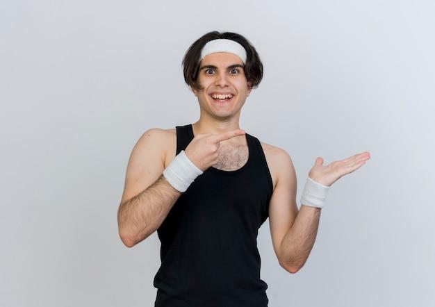 Młody sportowy mężczyzna ubrany w odzież sportową i opaskę z ręką wskazującą palcem wskazującym w bok, uśmiechnięty wesoło stojąc nad białą ścianą