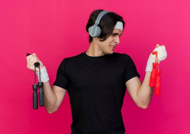 Młody sportowy mężczyzna ubrany w odzież sportową i opaskę ze słuchawkami, trzymając dwie skakanki, wyglądający na zdezorientowanego, próbując dokonać wyboru