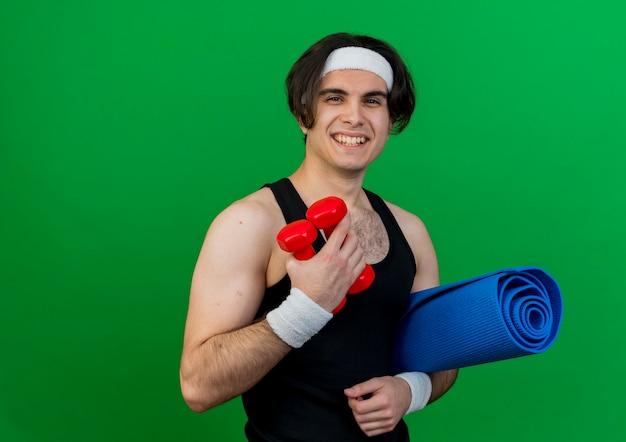 Młody sportowy mężczyzna ubrany w odzież sportową i pałąk, trzymając hantle i matę do jogi, uśmiechając się radośnie