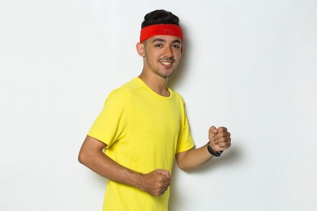 Młody sportowy mężczyzna ubrany w żółtą koszulkę biegnącą na białym tle