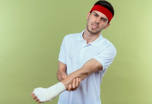 Młody sportowy mężczyzna w opasce dotykając jego zabandażowaną ręką czując ból stojąc na zielonym tle