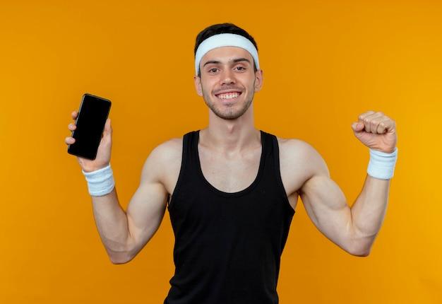 Młody sportowy mężczyzna w opasce pokazuje smartfon zaciskając pięść szczęśliwy i podekscytowany stojąc nad pomarańczową ścianą