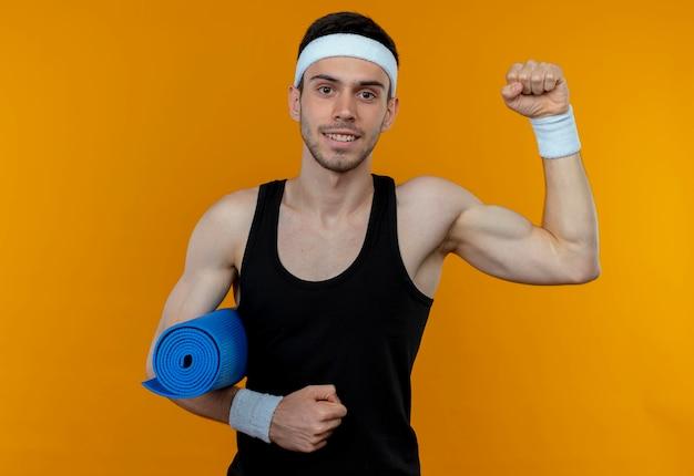 Młody sportowy mężczyzna w opasce trzyma matę do jogi podnosząc pięść uśmiechnięty stojący nad pomarańczową ścianą