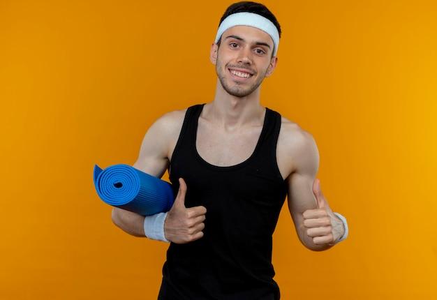 Młody sportowy mężczyzna w opasce trzyma matę do jogi uśmiechnięty pokazując kciuki do góry stojąc nad pomarańczową ścianą