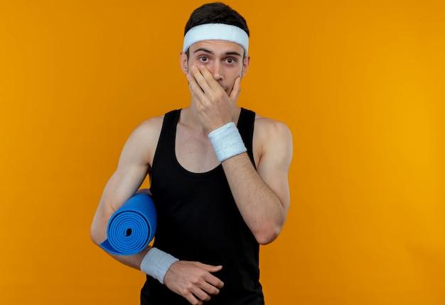 Młody sportowy mężczyzna w opasce trzyma matę do jogi zakrywającą usta ręką będąc w szoku stojąc na pomarańczowej ścianie