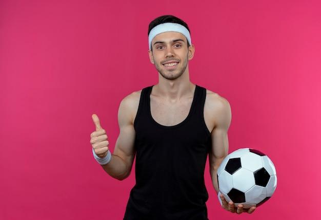 Młody sportowy mężczyzna w opasce trzyma piłkę nożną uśmiechnięty pokazując kciuki do góry stojąc nad różową ścianą