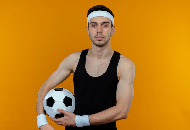 Młody sportowy mężczyzna w opasce trzyma piłkę nożną z pewną poważną miną stojąc nad pomarańczową ścianą