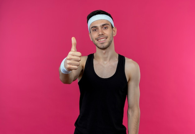 Młody sportowy mężczyzna w opasce uśmiechnięty szczęśliwy i pozytywny pokazując kciuki do góry stojąc nad różową ścianą