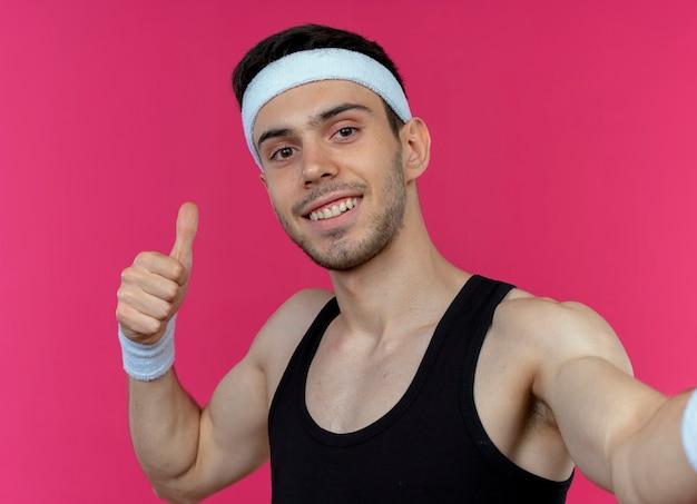 Młody sportowy mężczyzna w opasce wyświetlono kciuk w górę uśmiechnięty stojący nad różową ścianą