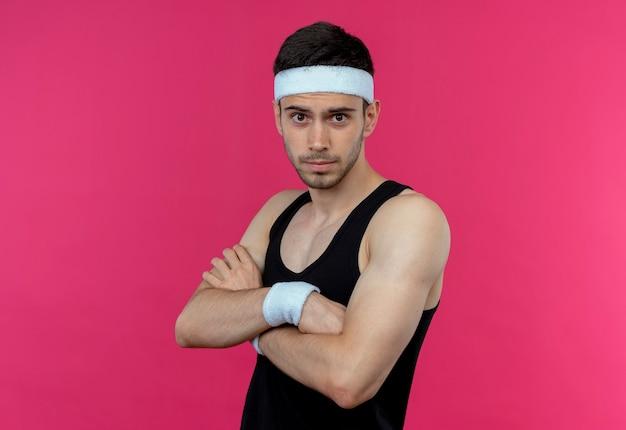 Młody sportowy mężczyzna w opasce z pewną siebie poważną miną ze skrzyżowanymi rękami na piersi, stojący nad różową ścianą