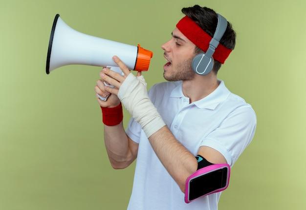 Młody sportowy mężczyzna w opasce ze słuchawkami i opaską na ramię smartfona krzycząc przez megafon stojący na zielonym tle