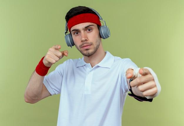 Młody sportowy mężczyzna w opasce ze słuchawkami i opaską na ramię smartfona, wskazując palcem na aparat, patrząc pewnie stojąc na zielonym tle