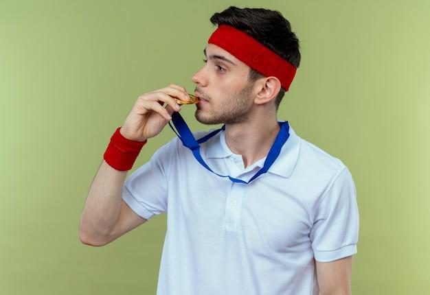 Młody sportowy mężczyzna w opasce ze złotym medalem na szyi, gryząc swój medal, patrząc pewnie na zielono
