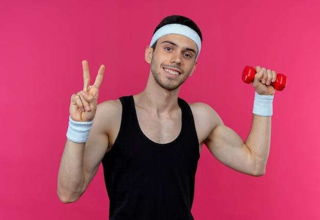 Młody sportowy mężczyzna w pałąku na głowę, ćwicząc z hantlami, patrząc na kamery, uśmiechając się, pokazując znak zwycięstwa stojący na różowym tle