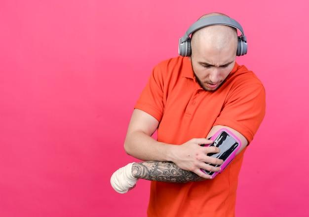 Młody sportowy mężczyzna z bandażem na nadgarstku, noszenie słuchawek i patrząc na opaskę na ramię telefonu na ramieniu na białym tle na różowej ścianie