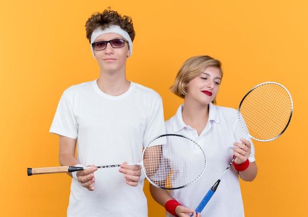 Młody sportowy para mężczyzna i kobieta trzyma rakiety do tenisa, uśmiechając się pewnie na pomarańczowo