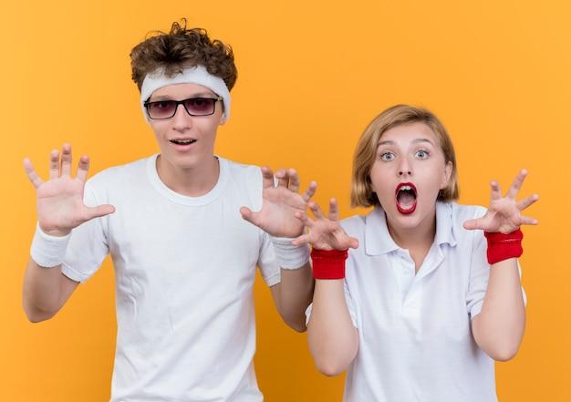 Młody sportowy para mężczyzna i kobieta z rękami na zewnątrz, uśmiechając się, zabawy stojąc nad pomarańczową ścianą